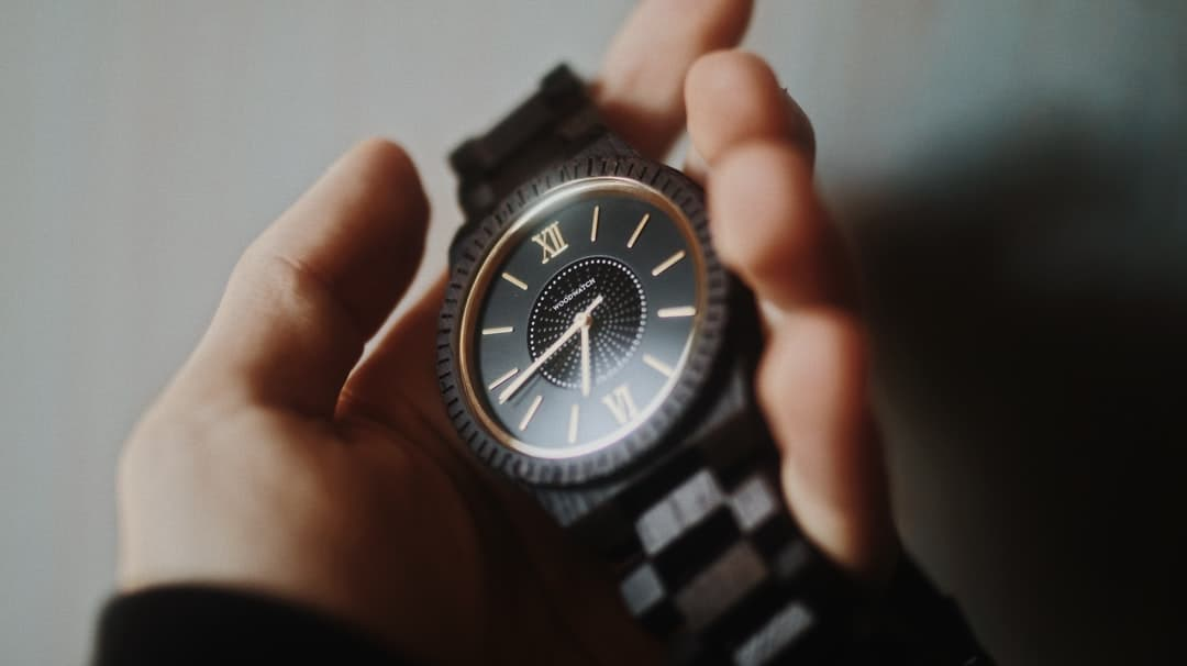 A hand holding a watch